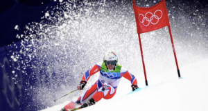 Olympic skier going down a mountain and rounding a marker